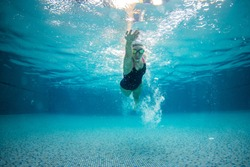 underwater picture of swimming woman in the pool.
