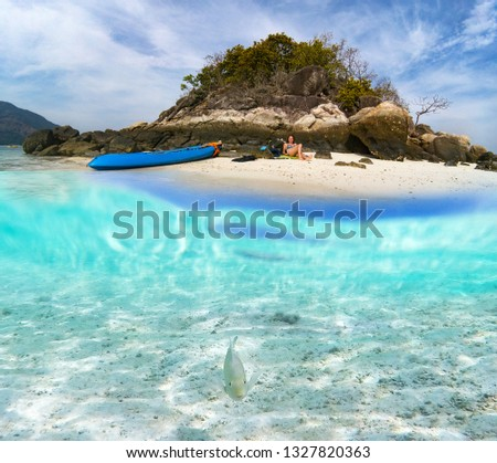 underwater picture of woman relaxing on paradise island with a kayak