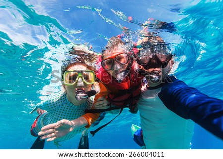 Shutterstock Underwater portrait of family snorkeling together at clear tropical ocean
