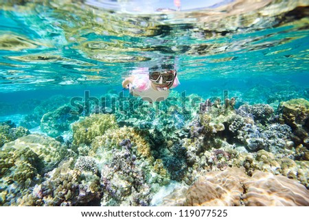 Underwater portrait of woman snorkeling at coral reef - stock photo