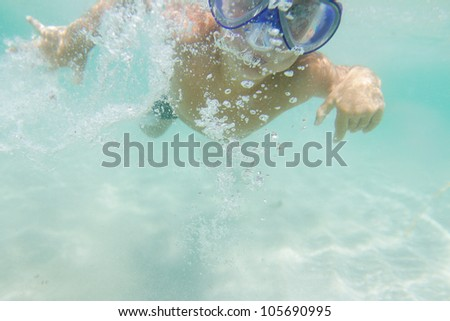 underwater portrait of young boy diving with scuba mask