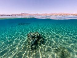 Underwater sea bottom view with half sky