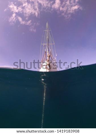 Underwater sea level photo of sail boat docked in open ocean sea #1419183908