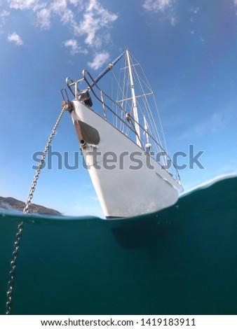 Underwater sea level photo of sail boat docked in open ocean sea #1419183911