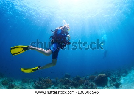 Underwater shoot of a divers swimming in a blue clear water Foto d'archivio ©