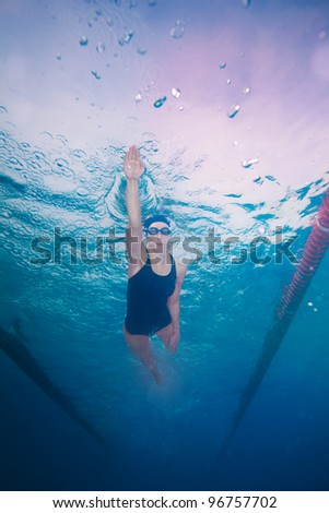 Underwater shoot of a professional woman swimming in crawl style