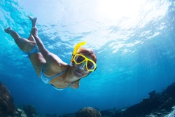Underwater shoot of a young lady snorkeling and doing skin diving in a tropical sea
