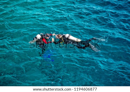 underwater, snorkeling divers in wetsuits equipped with snorkels, scuba, aqualung, diving masks, swim fins swimming in sea or ocean water on sunny day on blue background. Idyllic summer vacation #1194606877