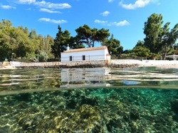 Underwater split photo of picturesque white washed chapel built by the sea in Greek island sandy beach