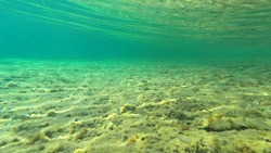 Underwater split photo of tropical exotic rocky bay with amazing emerald sea