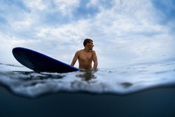 Underwater split shot of the young man surfer sitting on a board awaiting the waves