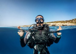 Underwater split view of a female scuba diver on the surface showing the OK sign with her hands