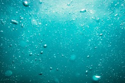 Underwater turquoise texture in ocean. Bubbles in tropical sea.