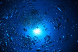 Underwater view deep down with air bubbles and sun in the open ocean