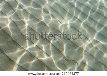 Underwater view of a clear ocean floor with sunlight shining through making a beautiful pattern on the sand.