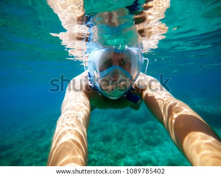 Underwater view of a young diver man swimming in the turquoise sea under the surface with snorkeling mask for summer vacation while taking a selfie with a stick. #1089785402