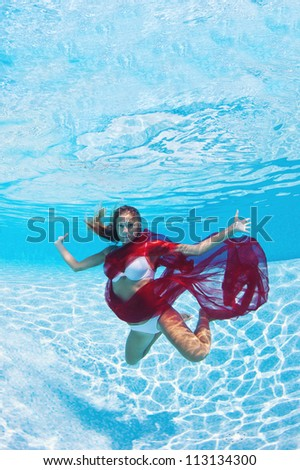 Underwater woman fashion portrait with red veil in swimming pool.
