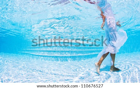 Underwater woman fashion portrait with white dress in swimming pool.