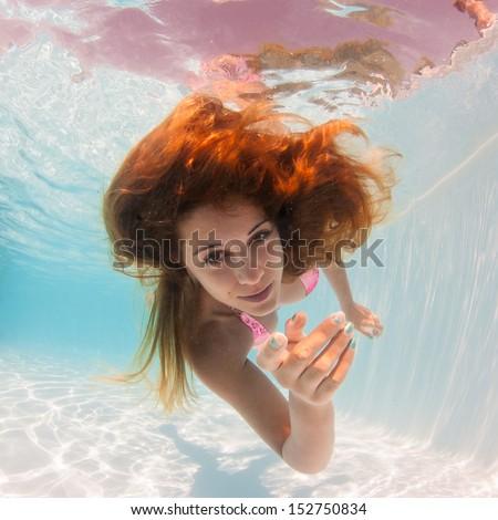 Stock Photo Underwater woman portrait in swimming pool.