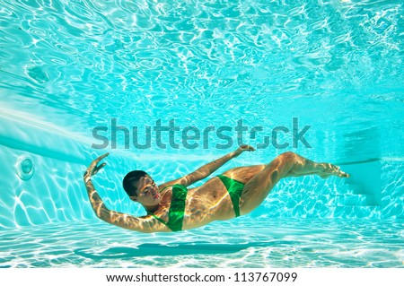 Underwater woman portrait with green bikini in swimming pool. Full body.