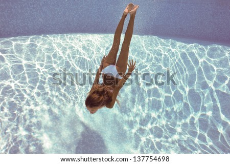 Stock Photo Underwater woman portrait with white bikini in swimming pool.