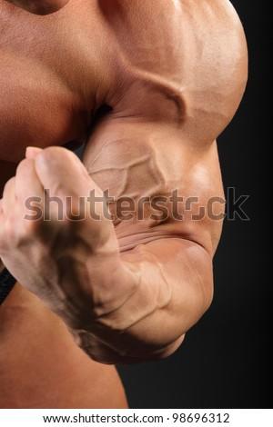 Undressed sunburnt bodybuilder demonstrates biceps in black studio