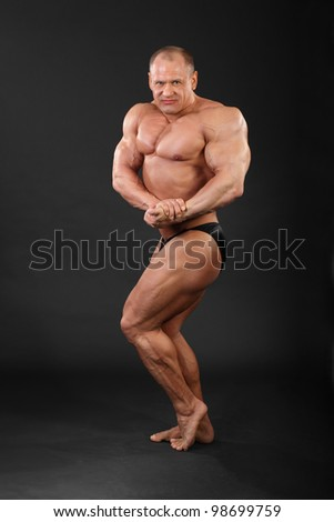 Undressed tanned bodybuilder demonstrates his arms and legs muscles