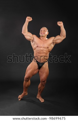 Undressed tanned smiling bodybuilder raises his fists up in black studio