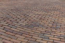 Undulating background of a street paved in red bricks, running bond pattern, horizontal aspect