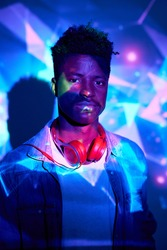 Unemotional African American male in casual outfit with headphones on neck standing in luminous neon lights in club and looking at camera