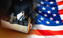 Unemployed. Man holds a box with personal belongings. USA flag. Concept - unemployed American. American was fired. USA resident is unemployed. Stationery in a cardboard box. American labor market