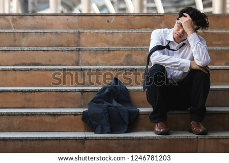 Unemployed stressed young Asian business man in suit covering face with hands. Failure and layoff concept.
