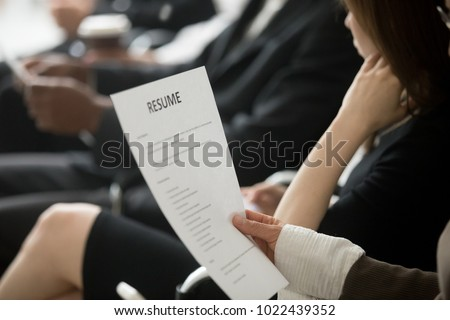 Unemployed woman applicant waiting in queue holding reading resume, vacancy candidate reading cv preparing for job interview, employment and hiring concept, curriculum vitae in hands close up view