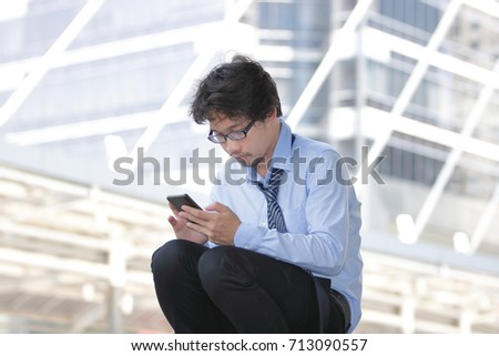 Unemployed young Asian man looking for job in mobile smart phone at city background. Unemployment concept.