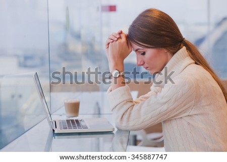 unemployment concept, problem, sad tired woman in front of laptop in modern bright cafe interior