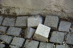 uneven cobblestones in vintage paving, bumpy paving stone surface of walkway