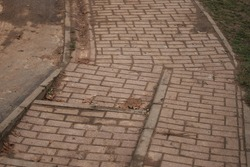 uneven paving slabs with cracks and gaps after poorly performed work on the improvement of pedestrian paths in the Park, violation of quality requirements by workers and corruption