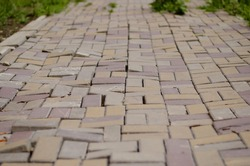 Uneven paving stones. Photo in perspective. An example of poor performance of the laid pavement. Photo of a sidewalk artificial stone of red color on an uneven road.
