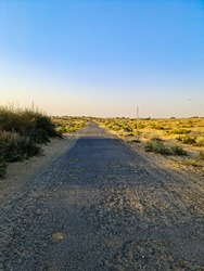 uneven road in the center of a desert.