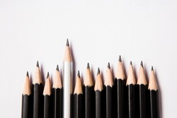 Uneven roll of black pencils with one silver pencil standing out. Black pencils are lower than the other one.