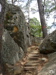 uneven stone steps in between huge rock formations in the jungle