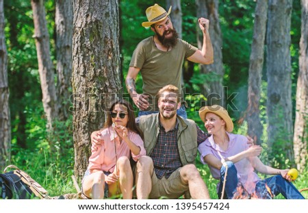 Unexpectable danger. Man brutal thief holds knife going attack hikers in forest. Company friends in dangerous situation in nature. Friends relaxing and not expect to be attacked. Be careful.