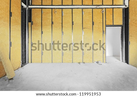 Unfinished building interior, walls covered with rock-wool.