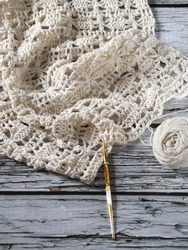 Unfinished crochet project using white yarns as material, following certain pattern in mixed stitches. Laid on white rustic wooden table. Concept of art, hobby, recreation, and creativity.