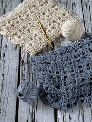 Unfinished crochet projects using grey and white yarns as material, following certain pattern in mixed stitches. Laid on white rustic wooden table. Concept of art, hobby, recreation, and creativity.