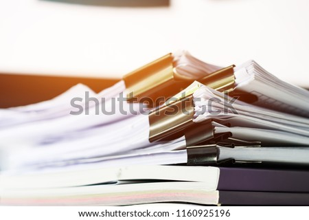 Unfinished documents stacks of paper files on office desk for report papers, piles of unfinish sheet achieves with black clips. Document is written presented. Business offices busy concept. #1160925196
