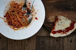 Unfinished eating pasta and last piece of homemade pizza still left on the wooden plate. Subject out of focus. No focus. Top view.