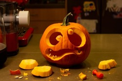 Unfinished jack-o-lantern on the kitchen counter. Funny halloween pumpkin face.