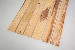 Unfinished raw pine lumber with light and dark color variation on a solid white background