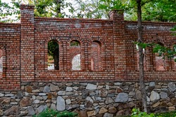 Unfinished red brick construction, old and textured stone. Large oval openings for the Windows, under the open sky among the trees and greenery